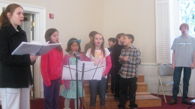 4-MIddleChoir (Photo of teens Steph and Matt singing with children)